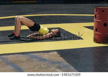 Fitness woman doing hip exercise workout on yoga mat outdoors. Fit girl model in sport clothes exercising, doing pelvic muscle exercises on roof at street