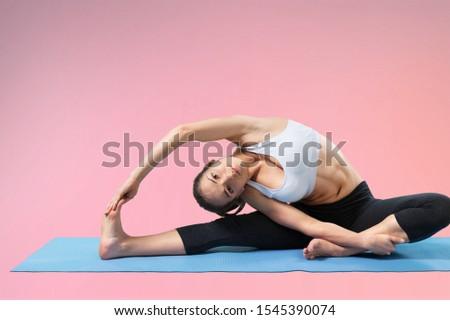 Fitness woman doing hip workout exercise on yoga mat at studio. Full length shot of fit girl model in sportswear exercising, doing pelvic muscle exercises on pink background