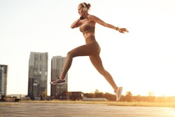 Fitness woman doing jumping exercise in sportswear and listening to music in headphones. Sporty girl, physical activity, motivation concept