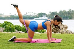 Fitness woman doing kickback exercise for glute with resistance band, outdoors. Athletic girl workout
