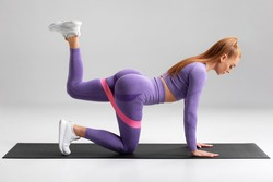 Fitness woman doing kickback exercise for glutes with resistance band on gray background. Athletic girl working out donkey kicks