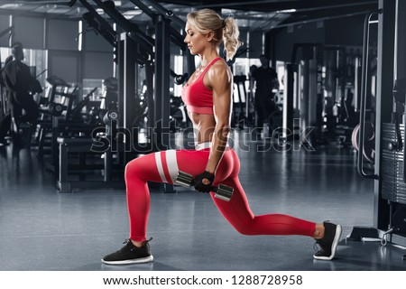 Fitness woman doing lunges exercises for leg muscle workout in gym. Active girl doing front forward one leg step lunge