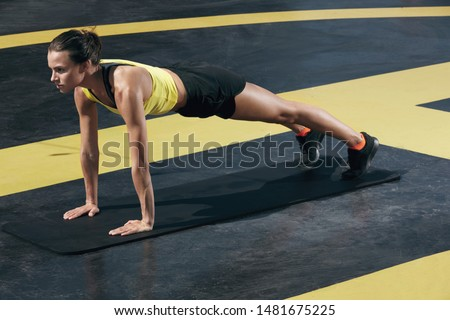 Fitness woman doing plank exercise workout in gym. Sport girl model in sportswear exercising on yoga mat, planking outdoors on street