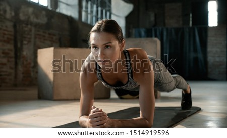 Fitness woman doing plank exercise workout in gym. Sport girl model in sportswear exercising on yoga mat, planking indoors