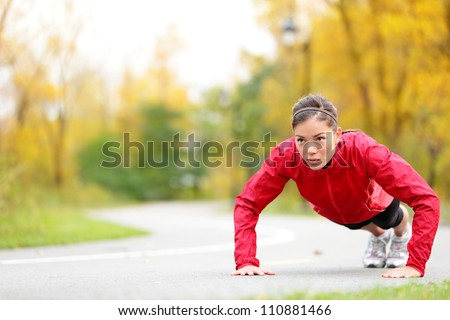 Fitness woman doing push-ups during outdoor cross training workout. Beautiful young and fit fitness sport model training outside in fall. - stock photo