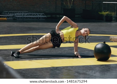 Fitness woman doing side plank exercise workout in gym. Sport girl model in sportswear exercising on yoga mat, planking outdoors on street