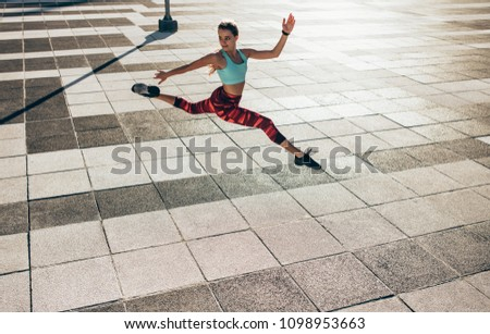Fitness woman doing split jump outdoors in the city. Flexible female athlete exercising outdoors. #1098953663