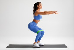 Fitness woman doing squats exercise for glute with resistance band on gray background. Athletic girl working out