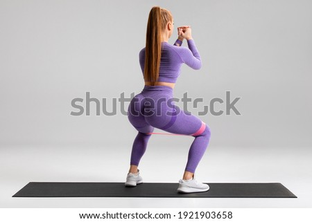 Fitness woman doing squats exercise for glute with resistance band on gray background. Athletic girl working out Photo stock ©