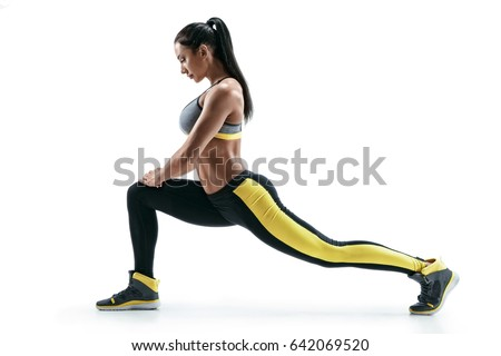 Fitness woman doing stretching workout. Full length shot of young woman on white background. Stretching and motivation