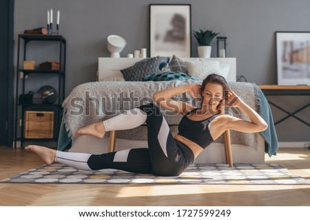 Photo of  Fitness woman doing twists exercise. Morning workout at home