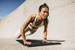 Fitness woman doing wide mountain climbers exercise. Female in sportswear exercising on fitness mat outdoors.