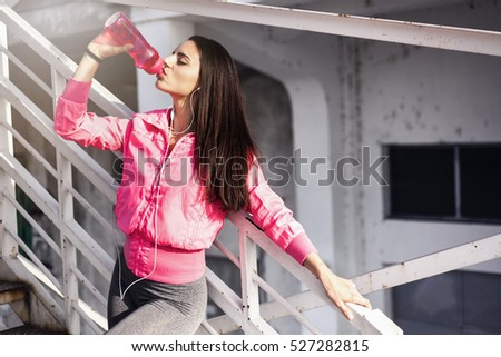 Fitness woman drinking water after jogging on metal steps