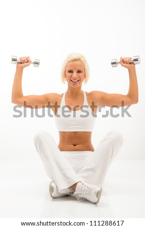 Fitness woman exercise in studio lifting dumbbells sitting white floor