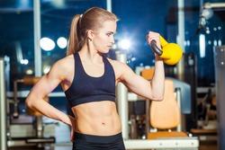Fitness woman exercising crossfit holding kettlebell strength training biceps