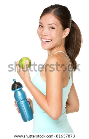 Fitness woman happy smiling holding apple and water bottle. Healthy lifestyle photo of Asian Caucasian fitness model isolated on white background.