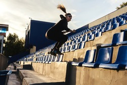 Fitness woman in black sportswear jumps on the stairs in stadium tribune. Street functional training, selective focus.