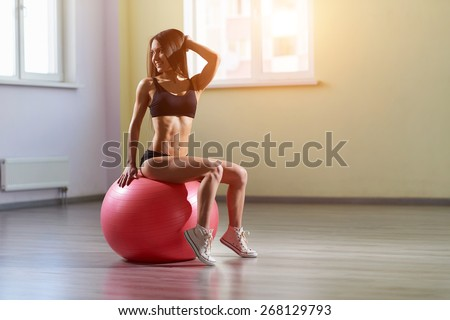 Fitness woman in gym resting on pilates ball. Young woman doing exercise on fitness ball. Young girl on the pink fitness ball in gym. Girl with fitness ball. Beautiful girl doing exercises with ball.