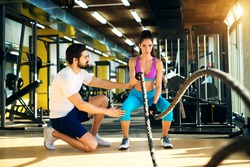 Fitness woman in training doing exercises with battle rope in the gym with a trainer next to her.