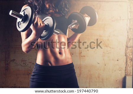 Fitness woman in training.Strong abs showing