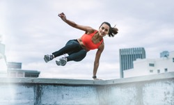 Fitness woman jumping on to the terrace from the rooftop fence with one hand on fence. Woman in fitness wear doing fitness training on rooftop.