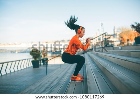 Fitness woman jumping outdoor in urban environment stock photo