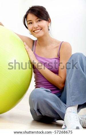 fitness woman leaning on a pilates ball and smiling