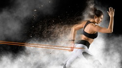 Fitness woman performs exercises with resistance band. Fitness model in sportswear on smoke background