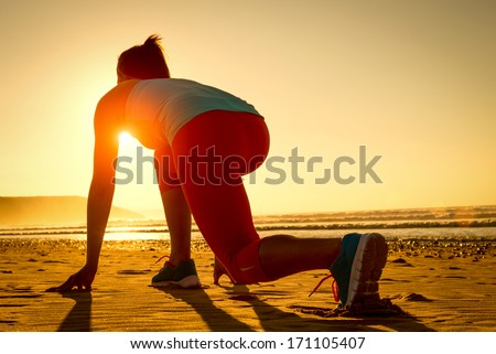 Fitness woman ready for running at sunset or sunrise on beach. Female athlete in powerful starting line pose.