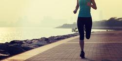 Fitness woman runner running on sunny coast trail