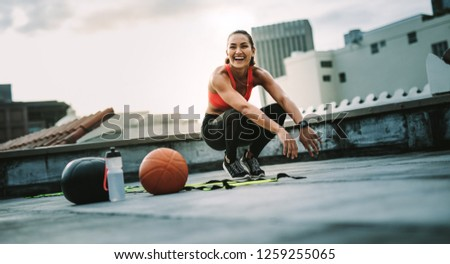 Fitness woman sitting on her toes while doing workout on rooftop. Cheerful woman athlete doing workout on rooftop with medicine ball and basketball by her side.