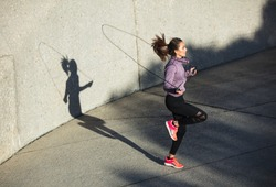 Fitness woman skipping with a jump rope outdoors. Female doing fitness training in morning.
