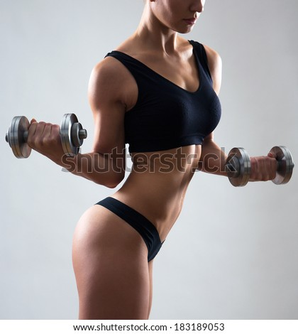 Fitness woman. Slim woman with dumbbells.