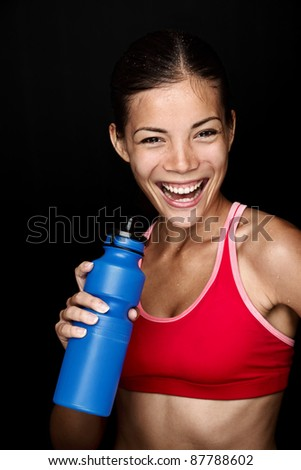 Fitness woman smiling with happy fresh energy while sweating and drinking water from bottle. Chinese Asian / white Caucasian female model on black background.