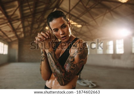 Fitness woman standing inside old factory. Tattooed woman after workout session in old warehouse.