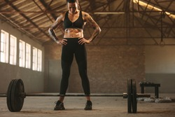 Fitness woman standing with barbells on floor at old warehouse. Female athlete getting ready to lift barbell.