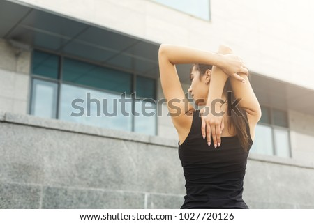 Fitness woman stretching her back before running outdoors, back view. Young slim girl makes aerobics exercise, gray wall background, copy space #1027720126