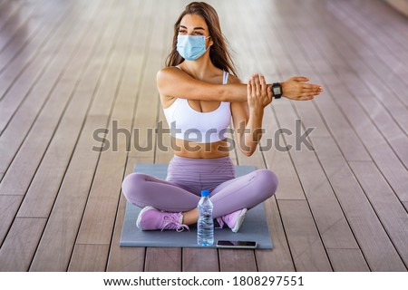 Fitness woman stretching outdoor with a face mask. One young woman doing stretching exercises and wearing a mask. Woman with a protective face mask stretching and exercising outdoors