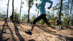 Fitness woman trail runner running on sunrise tropical forest mountain peak