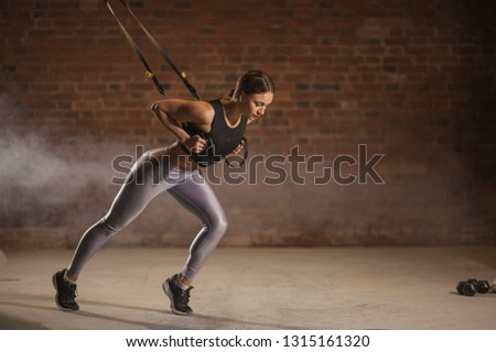 Fitness woman trainig in the gym, doing Sprinter Start exercise where stabilizing muscles are trained and the whole body is working, which makes such workouts truly functional.