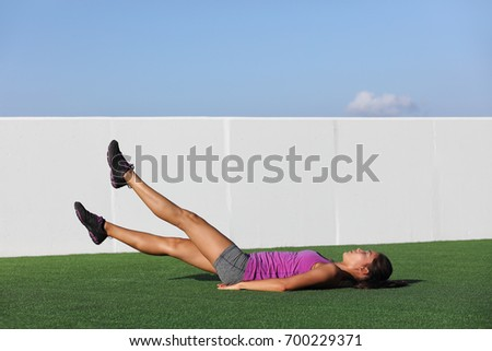 Fitness woman training abs workout doing scissor lifts leg raise or flutter kicks exercise out outdoor grass floor at gym.
