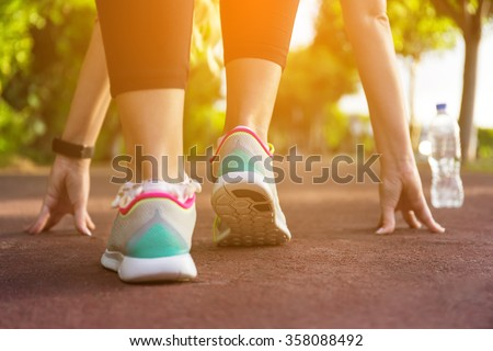 Fitness woman training and jogging in summer park. Ready to start. Healthy lifestyle and sport concept