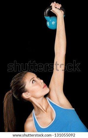 Fitness woman training with kettlebell Fit beautiful multicultural fitness instructor isolated on black background