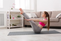 Fitness, woman training yoga in boat pose at home. Young slim girl makes exercise.