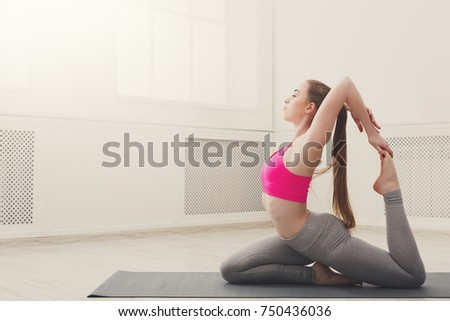 Stock Photo Fitness, woman training yoga in camel pose in gym at white background, copy space. Young slim girl makes exercise.
