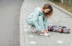 Fitness woman tying shoelaces outdoors