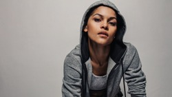 Fitness woman wearing a hoodie jacket staring at camera. Healthy female in sportswear against grey background.