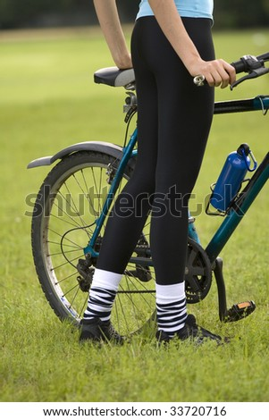 fitness woman with a bike posing outdoor, close up shot of female legs