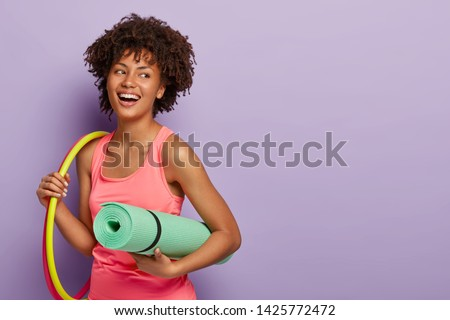 Fitness woman with dark skin, works with hula hoops, holds rolled karemat for training, laughs joyfully, satisfied after workout, looks healthy and fit wears rosy t shirt isolated on purple background