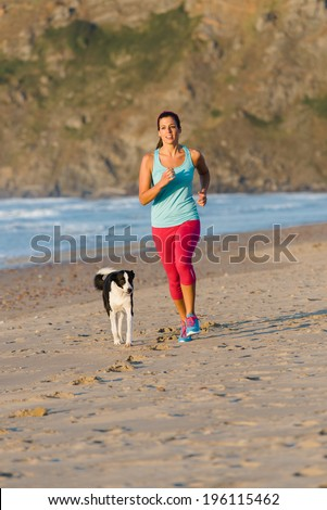 Fitness woman with dog running and exercising at beach on summer. Brunette female athlete training with her pet.